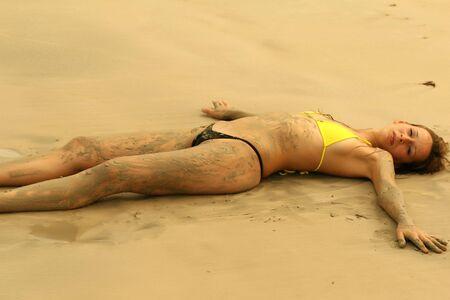 bikini girl lying on the beach by sunset photo