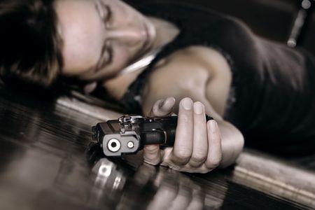 dead woman lying on the floor, gun in the hand photo