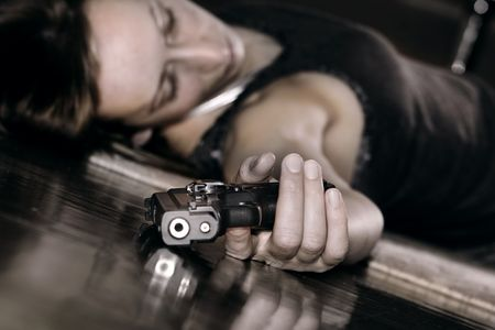 dead woman lying on the floor, gun in the hand photo