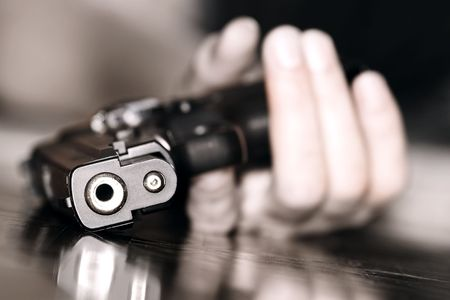 close up of gun in the female hand Stock Photo