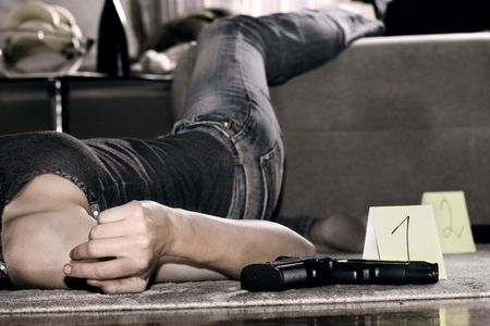 dead woman lying on the floor, gun on the floor photo