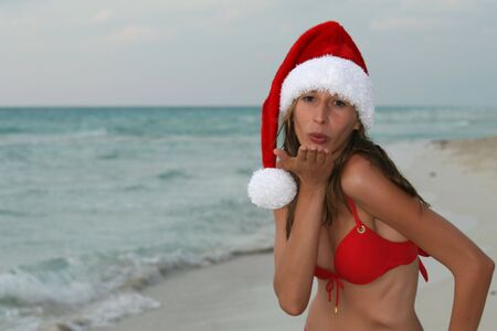 woman wearing red bikinis and santa hat on the beach photo