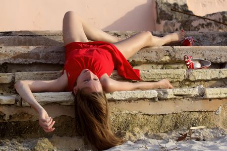drunk girl: woman playing dead, lying on the stairs Stock Photo