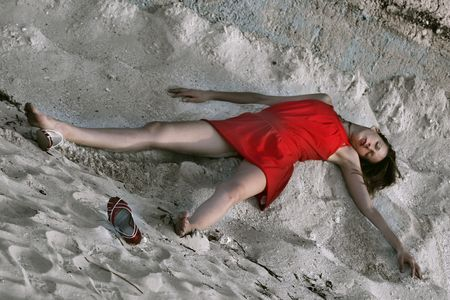 beautiful woman playing dead, lying in the sand