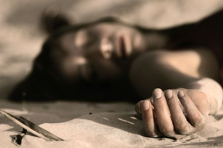 woman playing dead, lying in the sand photo