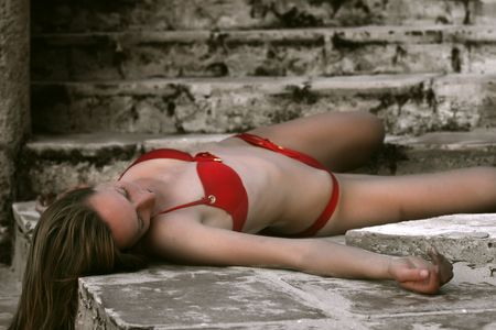 actress: woman in red bikini playing dead, lying on the stairs Stock Photo