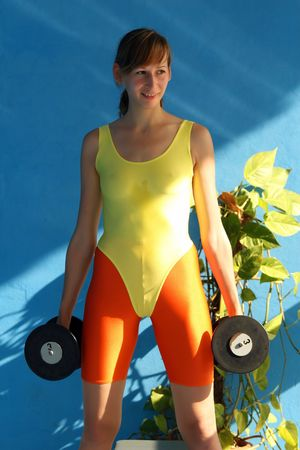 lycra: Woman doing exercises with dumbbells in the fitness center