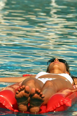 Woman Lying On An Air Matress In Blue Pool Stock Photo - 3804238