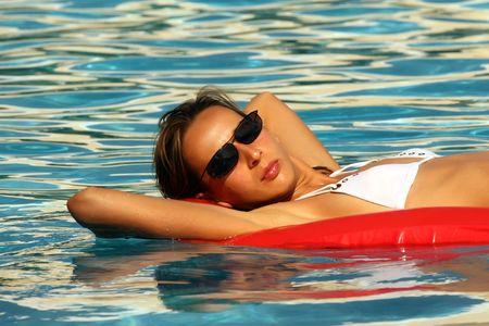 matress: Woman swimming On An Air Matress In Blue Pool Stock Photo