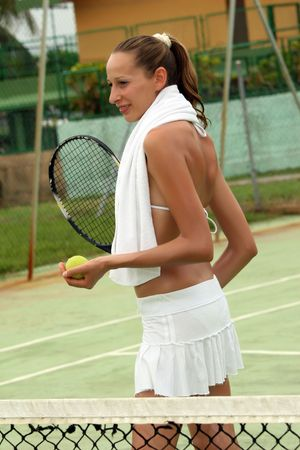 tennis skirt: woman in white skirt holding tennis racket with ball outdoor