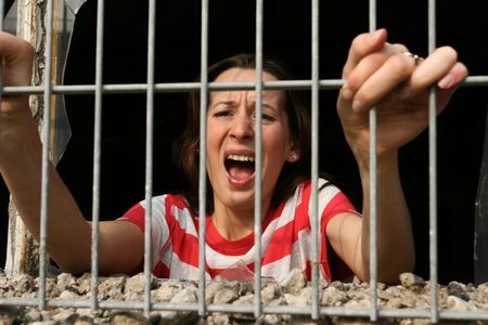 woman behind bars in old prison screaming photo