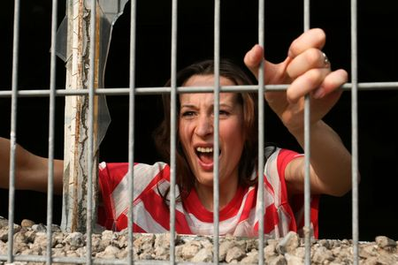 woman behind bars in old jail, screaming photo