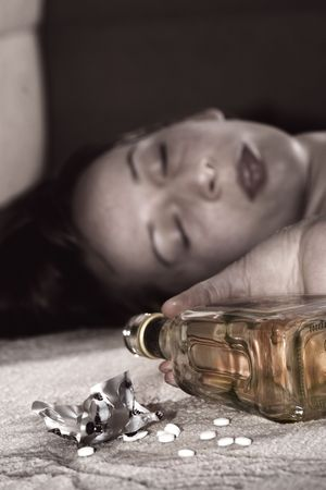dead woman lying on the floor, bottle of whisky in the hand and pills on the carpet photo