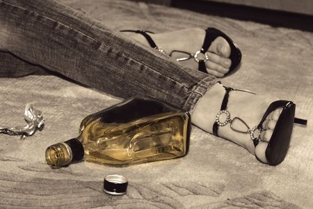 dead woman lying on the floor, bottle of whisky and pills near her legs photo