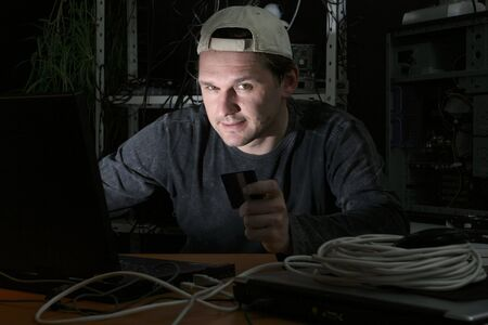 hacker on computer holding a credit card Stock Photo - 4708674