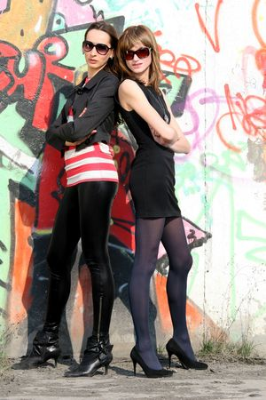 two female fashion girls posing at the wall Stock Photo - 4830529
