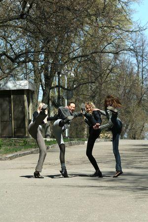 four female friends kicking kicking on the street Stock Photo - 4833649