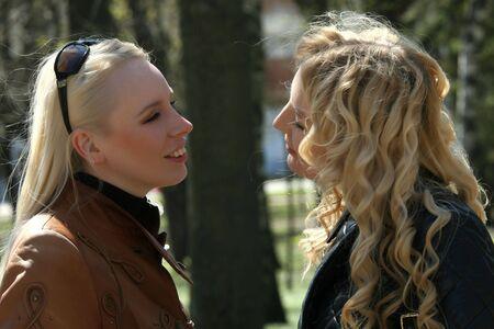 two friends talking: two friends talking in a park