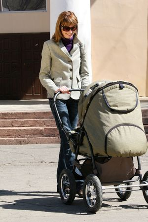 happy mother with baby carriage in city park