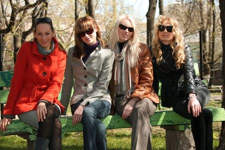four women friends relaxing on the bench in a city park Stock Photo - 4833522