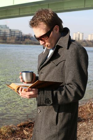 man reading book und drinking tea outdoor Stock Photo - 4880303