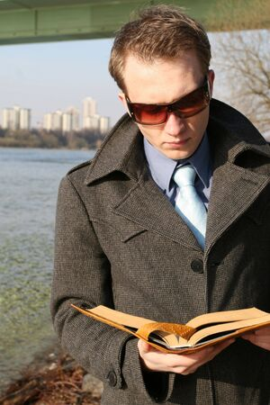 businessman reading book outdoor by the river photo