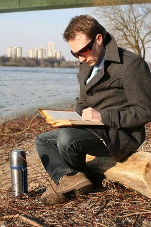 man reading book und drinking tea outdoor photo