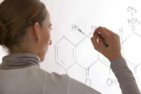 woman writing a molecular structure on whiteboard  photo