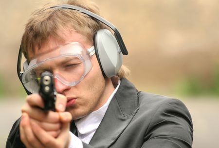 Male police officer aiming with gun into the camera Stock Photo - 5000707