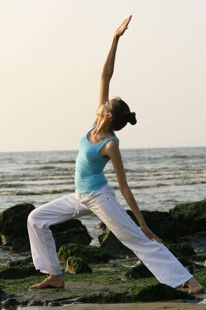 woman doing yoga exercises at the beach photo