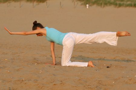woman doing yoga workout at the beach photo