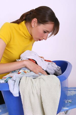 woman looking at Laundry basket with dirty clothing Stock Photo - 5183256