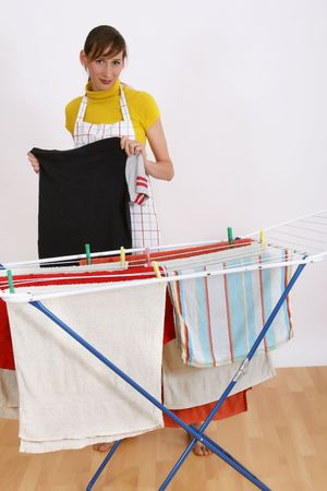 woman hanging towels and shirts on the rack photo