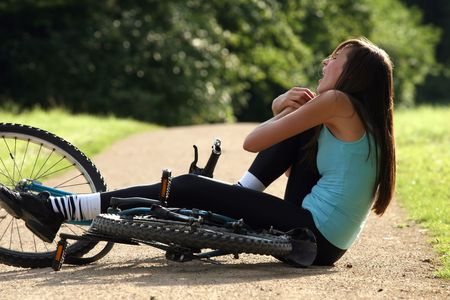 stunned: Female bike rider takes a tumble and holding her knee from pain