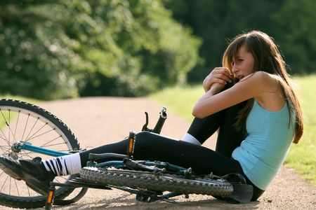 Female bike rider takes a tumble and crying from pain Stock Photo