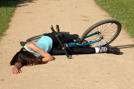 crash: Female bike rider takes a tumble and lying unconscious on the road
