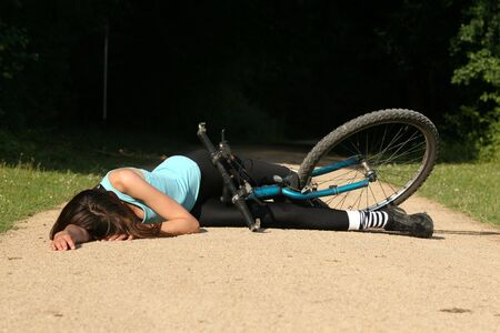 unconscious: Female bike rider takes a tumble and lying unconscious on the road