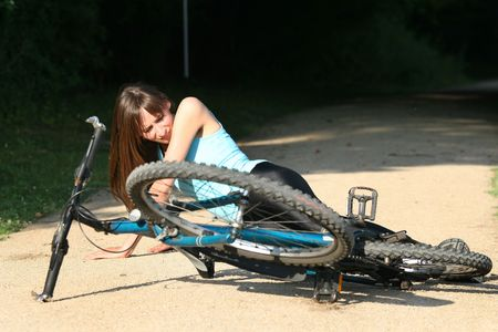 Female bike rider takes a tumble and lying in pain on the road Stock Photo