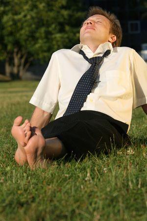 tired businessman: happy businessman enjoying the sun in a city park