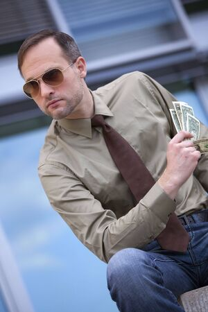businessman in sunglasses holding the money on the street photo