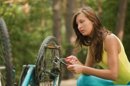 woman repairs a bike in the forest photo