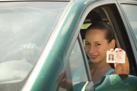 licence: happy woman holding driving licence in a car Stock Photo