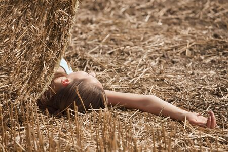 young woman lying dead in the field Stock Photo