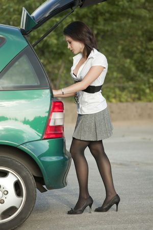 young female standing at the rear of a car Stock Photo - 5442510