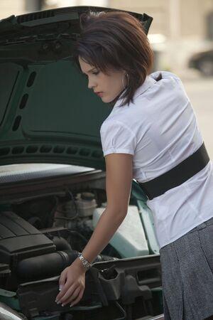 sich b�cken: junge weibliche Biegung �ber eine Auto-engine