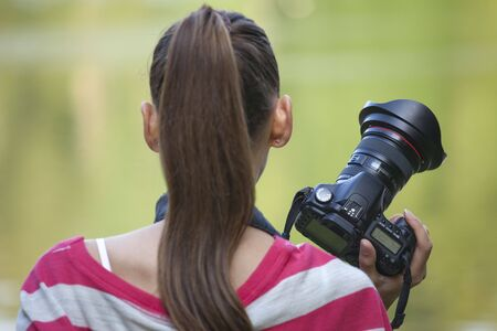 Female Photographer with professional camera in a park photo
