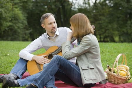picknick: man playing guitar by romantic picknick outdoors