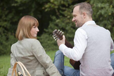 picknick: man playing acoustic guitar by romantic picknick Stock Photo