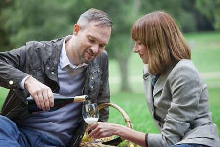 man pours champagne into a glass by romantic picnic photo