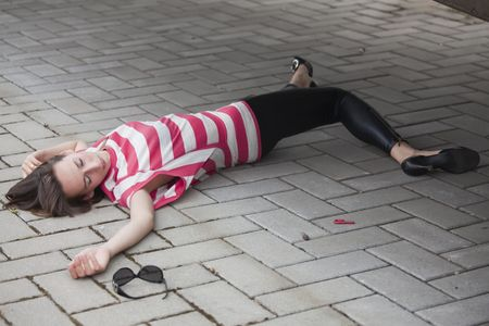 unconscious: dead woman lying on asphalt road